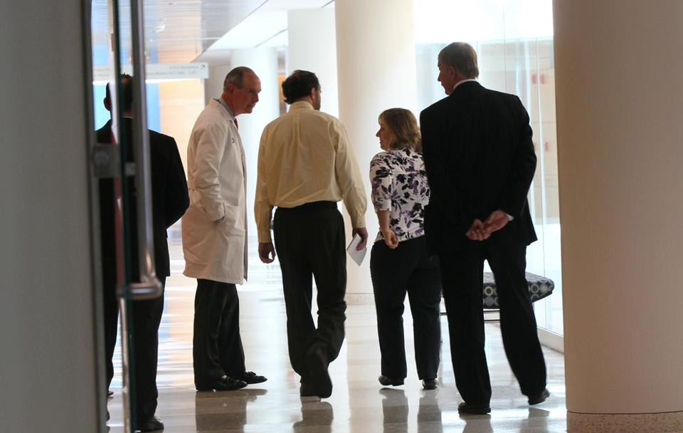 Dr. Richard Sacra (second from left) walked away from a news conference held Friday at UMass Medical Center in Worcester.